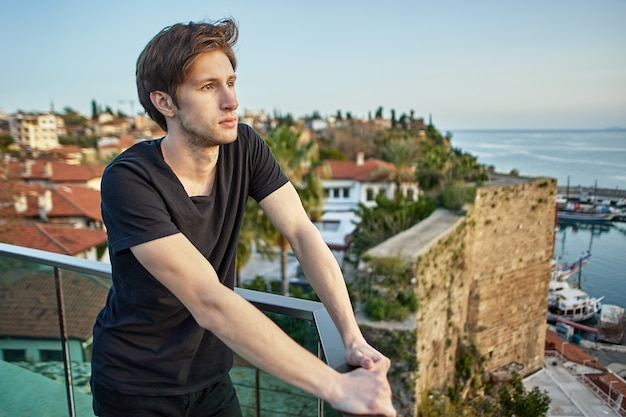 Задумчивый европейский мужчина смотрит на старый город в анталии с выгодной позиции