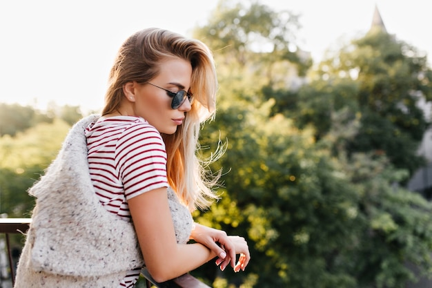 Pensive european woman in sunglasses enjoying nature view while stands on terrace