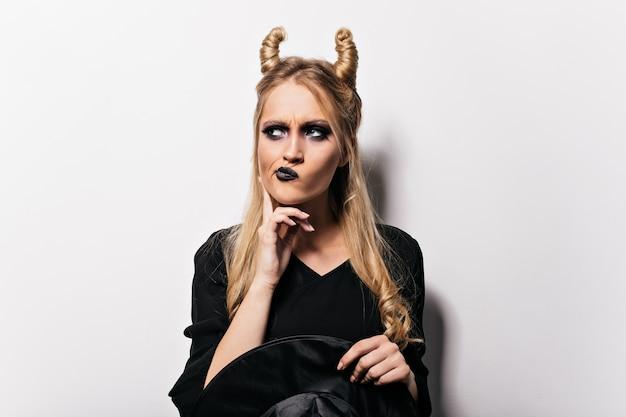 白い壁にポーズをとる物思いにふける邪悪な魔女。好奇心旺盛なブロンドの女の子のハロウィーンの肖像画。