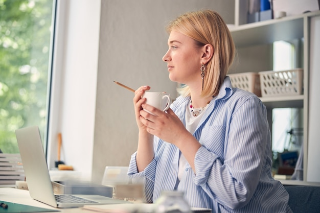 Pensive female looking away while resting with a cup of hot drink in office