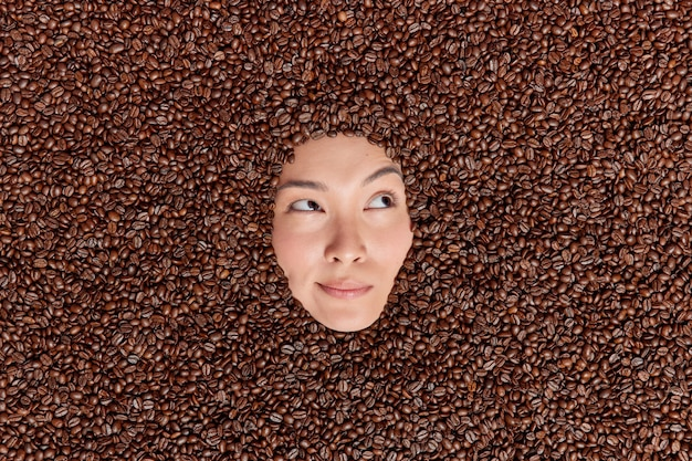 Pensive female model drowned in brown coffee beans looks thoughtfully away uses roasted seeds for preparing refreshing beverage to boost energy or making skin scrub enjoys pleasant fragrance