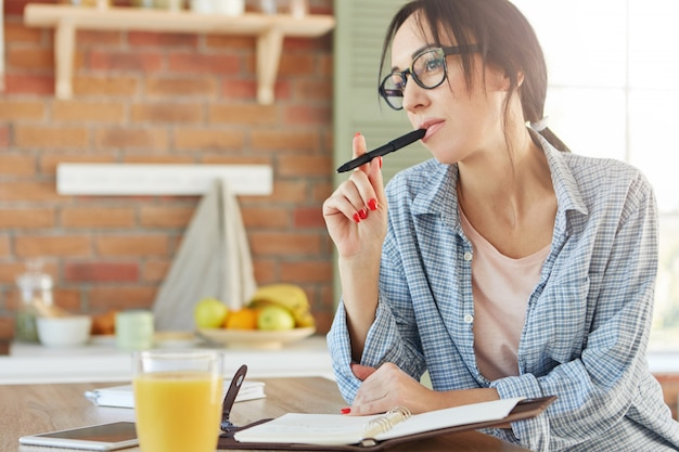 Pensive female model keeps pen, writes recipe in notepad, tries to remember all necessary ingredients