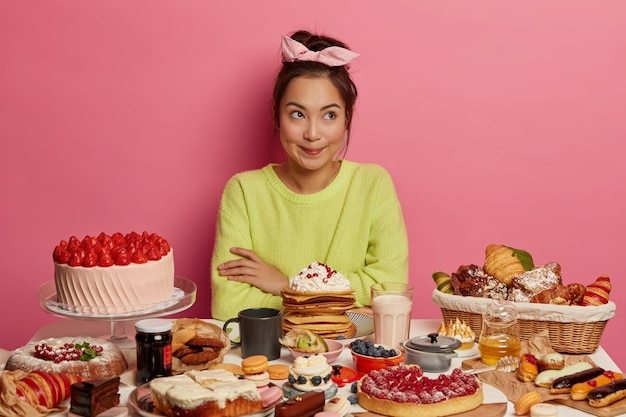 Pensive female sweet tooth enjoys eating sweet desserts, poses at table full of tasty cakes, pancakes, cookies, drinks coffee or milk, surrounded by junk food containing much sugar.