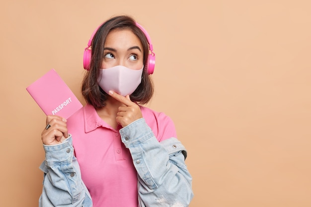 Pensive female traveler going to have fright abroad during coronavirus pandemic wears protective face mask holds passport listens music via headphones looks away wears t shirt and denim jacket