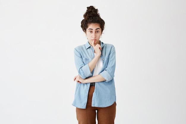 お団子の黒い髪の物思いに沈んだ女性は問題を解決することを考え、唇に指を置き続け、方法を予測しようとします、外見、広告用のコピースペースがある白い壁にポーズをとります