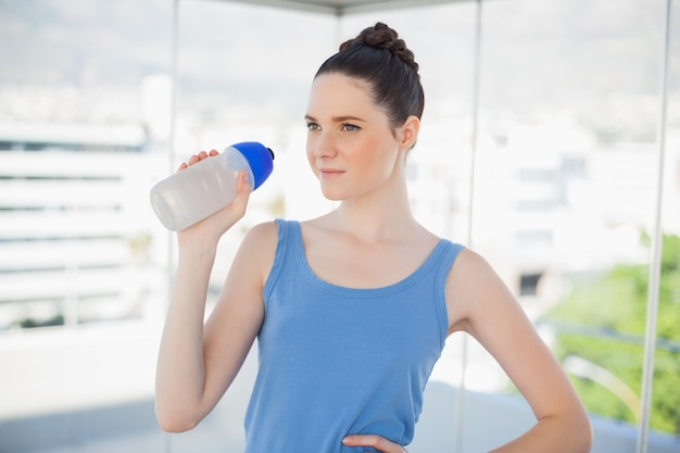Pensive fit woman holding plastic flask