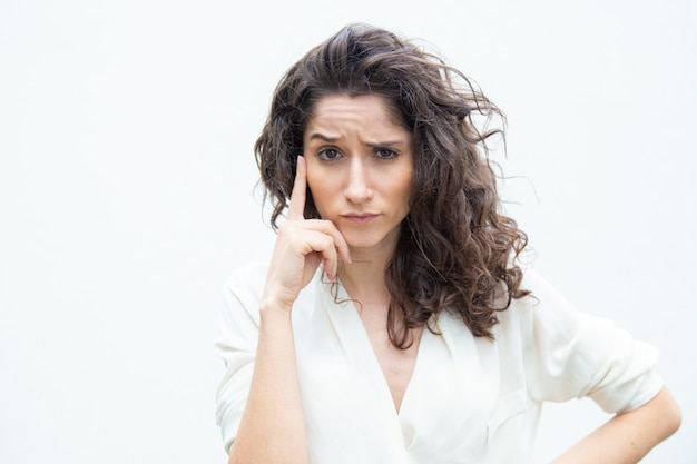 Pensive focused female customer touching face with finger