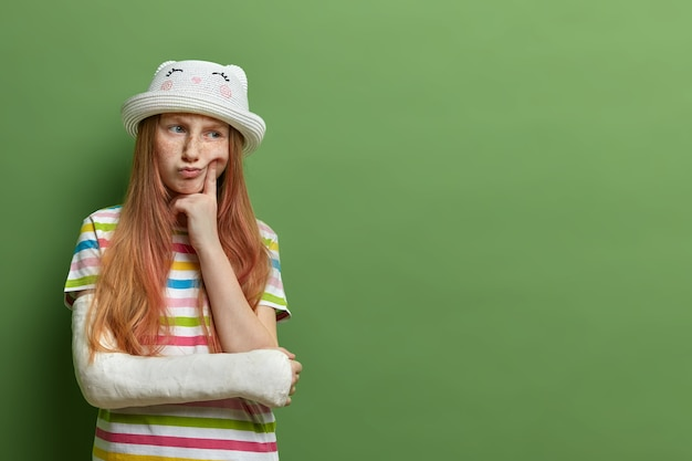 Задумчивая веснушчатая девочка с рыжими волосами, держит палец на щеке, с недовольным выражением лица, сломала руку, не может играть с детьми на улице, изолирована на зеленой стене, пустое место для рекламы
