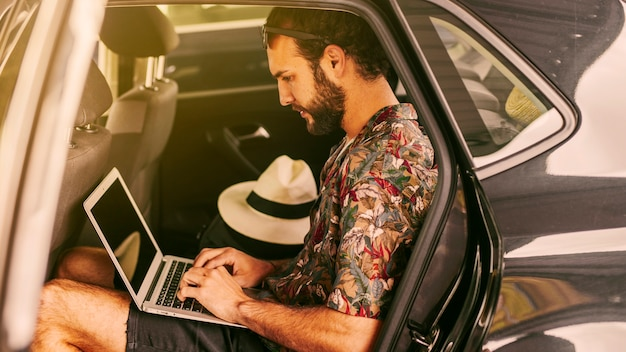 Pensive freelancer working remotely in car