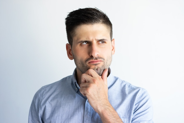 Pensive frowning guy in casual making decision