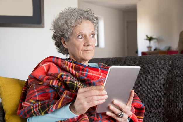 Pensive frowning senior woman reading online book on tablet