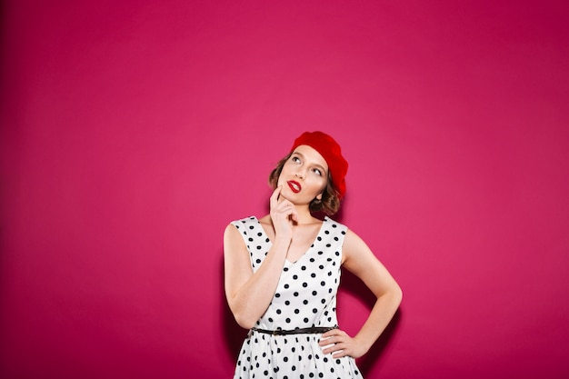 Pensive ginger woman in dress with arm on hip holding her chin and looking up over pink