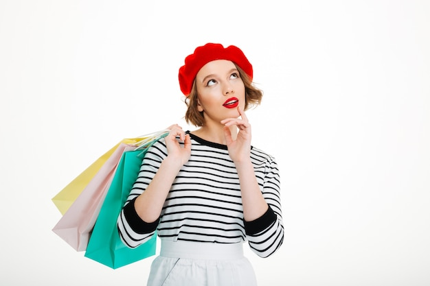 Pensive ginger woman holding packages and looking up while holding her chin over grey