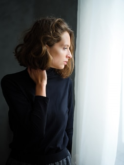 Pensive girl in black pullover near the window