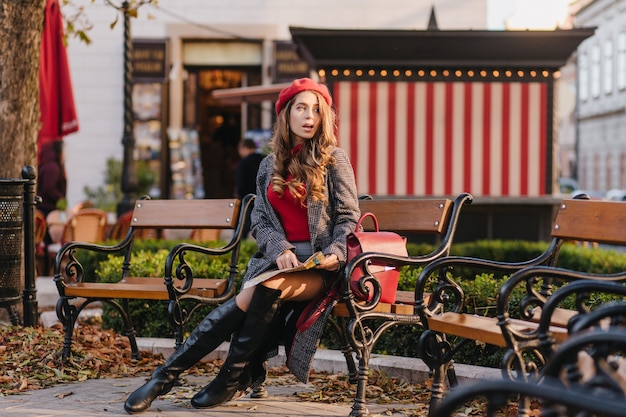 Задумчивая девушка в сапогах до колена сидит на скамейке и смотрит в сторону с открытым ртом