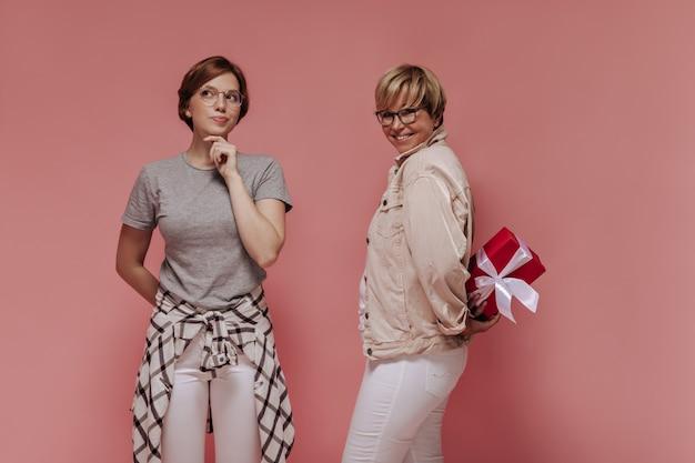 Задумчивая девушка в клетчатой рубашке и очках позирует с улыбающейся женщиной в бело-бежевой одежде с подарочной коробкой на изолированном фоне.