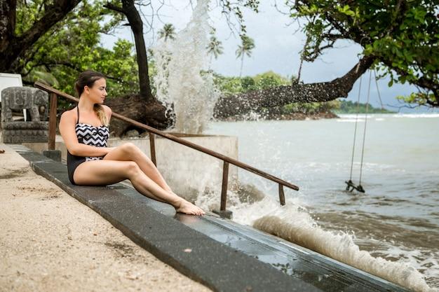 荒れ狂う海の階段に座っている黒い部分の水着で物思いにふける女の子