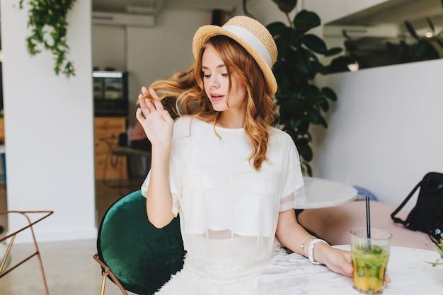 レストランで彼氏を待っている間、光沢のあるカールで遊んでいるトレンディな白い服装の物思いにふける女の子