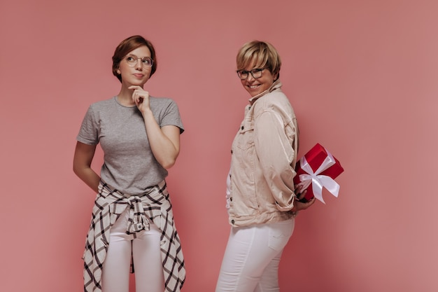 Pensive girl in plaid shirt and glasses posing with smiling woman in white and beige clothes with gift box on isolated background.