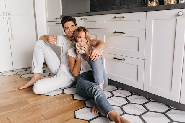 一杯のコーヒーと床に座っている物思いにふける女の子。一緒にお茶を楽しんで幸せなカップル。
