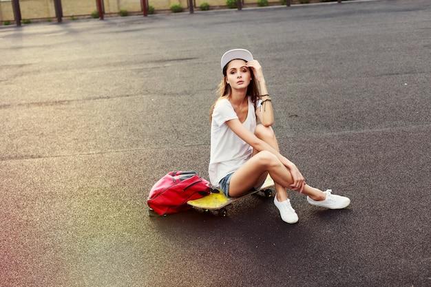 日没時にスケートボードの上に座って物思い女の子