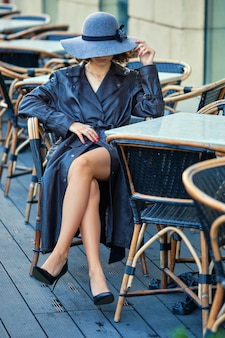 Pensive girl sitting behind a table at cafe terrace in leather coat and felt hat
