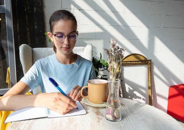 생각에 잠긴 여학생은 공책에 펜으로 과제를 씁니다. 안경을 쓰고 대각선 그림자가 있는 카페에서 파란색 블라우스를 입은 백인 갈색 머리 소녀의 초상화. 종이 책 읽기의 개념