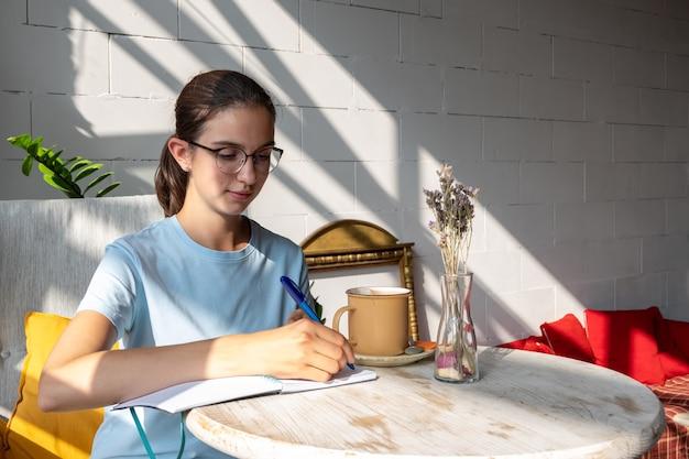 생각에 잠긴 여학생은 공책에 펜으로 과제를 씁니다. 안경을 쓰고 대각선 그림자가 있는 카페에서 파란색 블라우스를 입은 백인 갈색 머리 소녀의 초상화.