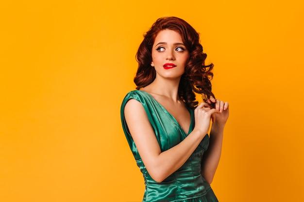 黄色い空間で巻き毛に触れる物思いにふける少女。緑のドレスを着た思いやりのある女性のスタジオショット。