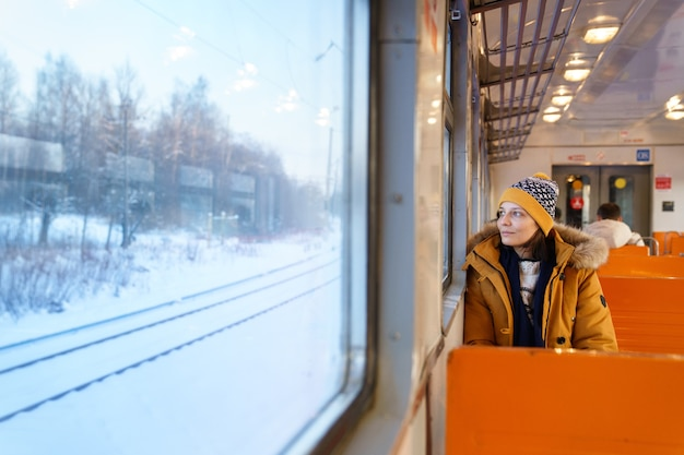 Pensive girl traveling by local train in winter time, looking through the window at snowy landscape