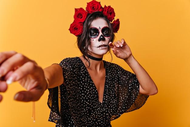 그녀를 따르라고 요구하는 갈색 눈의 슬픈 표정으로 잠겨있는 소녀. 오렌지 벽에 검은 머리 멕시코 모델의 초상화.