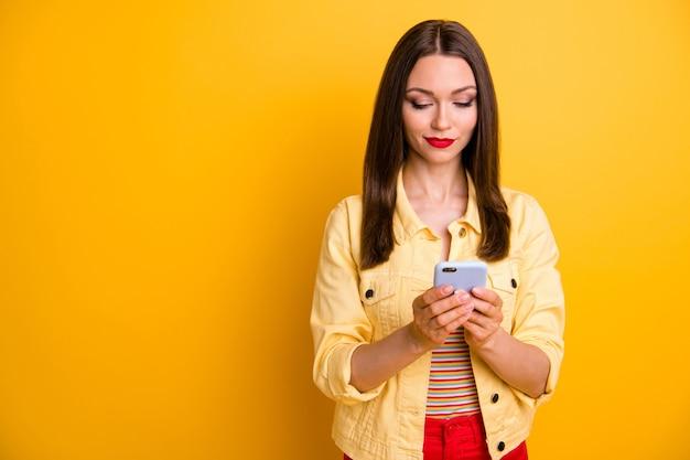 物思いにふけるガールフレンドは、唇のポマード孤立した鮮やかな色の壁と空のスペースの近くに立って電話ブラウジングを探しています