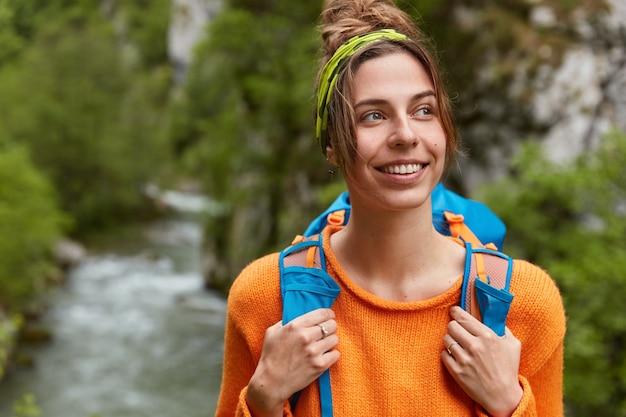 잠겨있는 기쁜 여성이 장엄한 곳을 여행하고, 행복하게 외모를, 캐주얼 오렌지 스웨터를 입고, 배낭을 나 릅니다.