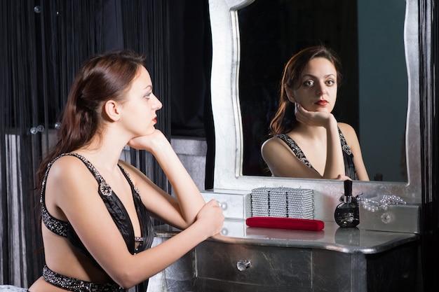 Задумчивая гламурная задумчивая молодая женщина в вечернем наряде сидит за туалетным столиком, отражается в зеркале с выражением тоски на лице