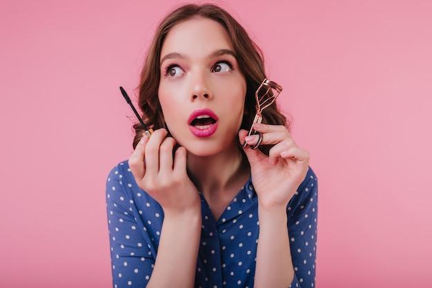 Задумчивая гламурная молодая женщина держит тушь и смотрит в сторону с открытым ртом. модная девушка завивает ресницы перед свиданием.