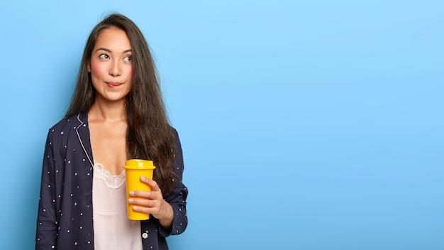 Задумчивая красивая девочка-подросток с длинными прямыми волосами, кусает губы и что-то думает, пока пьет утренний кофе, носит пижаму