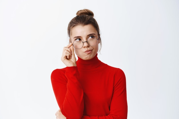 Pensive good-looking woman in glasses thinking, looking right side at empty space and pondering, standing thoughtful against white wall