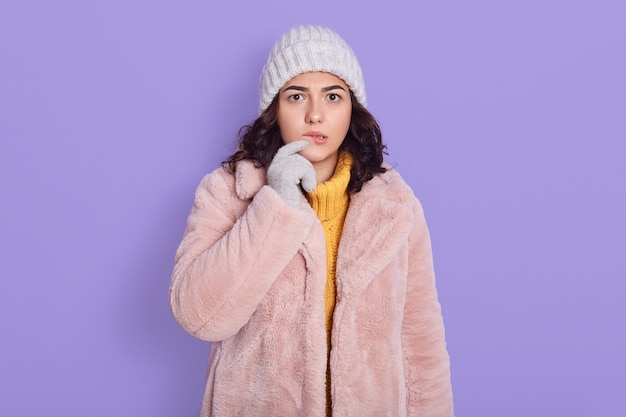 Pensive good looking young woman with dark hair looking thoughtfully at camera, dressed in fashionable pink coat and cap, looking concentrated, poses against blue background, keeping finger on lip.