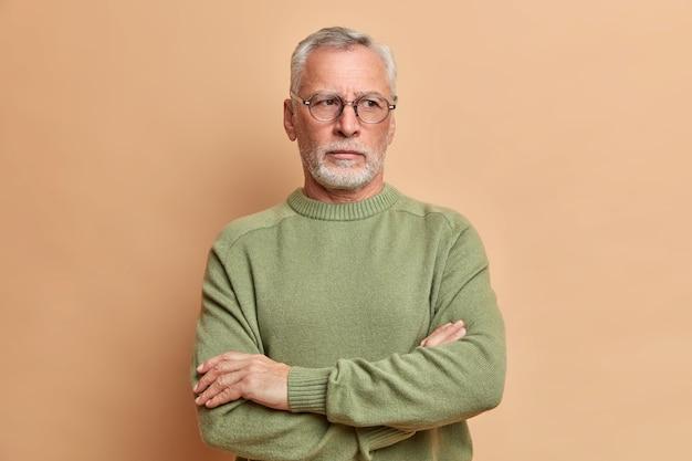 잠겨있는 회색 머리 수염 난 노인은 팔을 교차하고 멀리 보이는 캐주얼 점퍼를 입고 주말에 갈색 스튜디오 벽 위에 고립 된 아이들을 방문 할 계획을 숙고합니다.