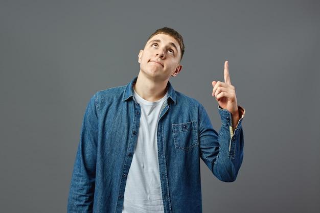 白いtシャツとジーンズのシャツを着た物思いにふける男は、スタジオの灰色の背景に指を指しています。