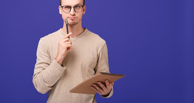 Pensive guy editor with brown notebook and black pen near his face looks straight