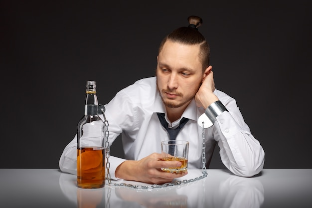 Pensive guy holding a glass of whiskey