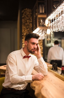 Pensive guy sitting at bar counter