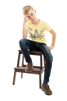 Pensive guy teenager in jeans and a yellow t-shirt is sitting on a chair isolated over white background.