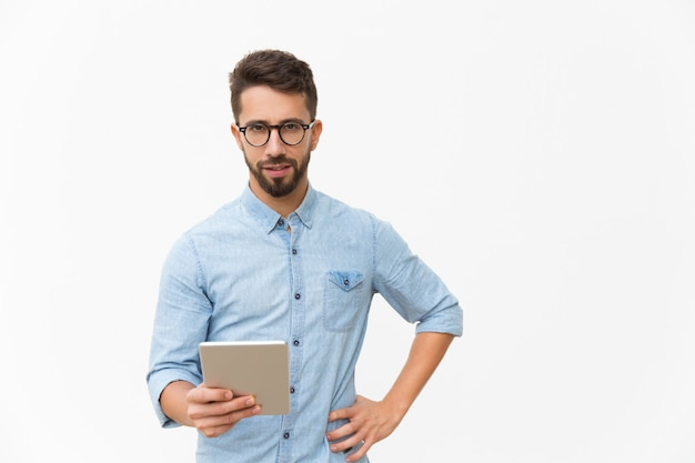 Pensive guy using tablet, holding device