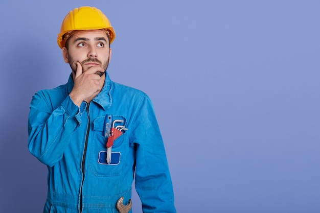 Pensive guy wearing yellow helmet and blue overalls, boy with wrench, looking aside with thoughtful facial expression
