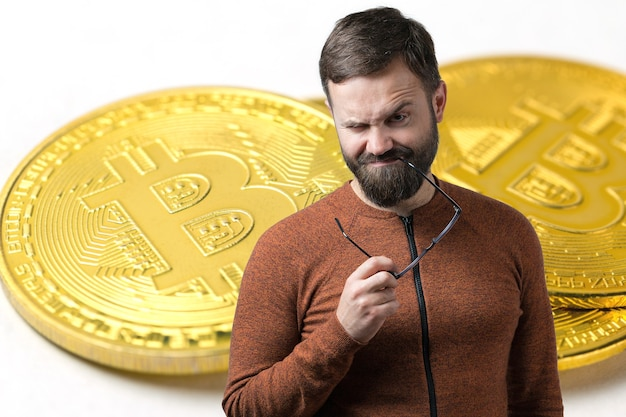 A pensive guy with a beard and glasses against a background of bitcoin thinking about question