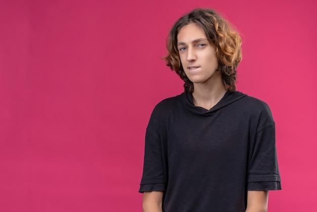 Задумчивый парень с длинными волосами в черной футболке на розовой стене