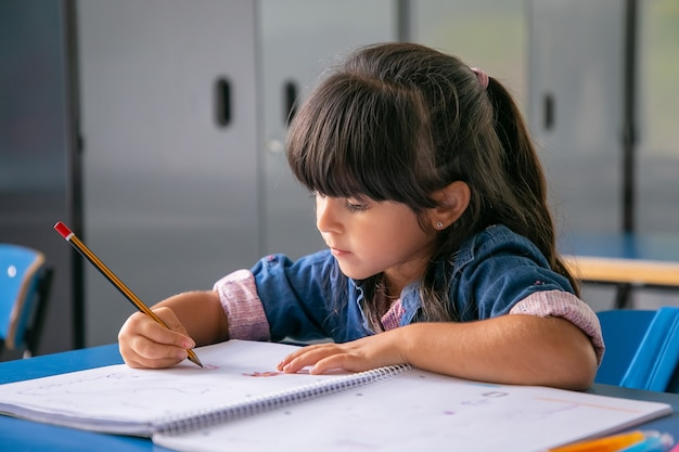 Pensive haired latin girl sitting at school desk and drawing in her copybook