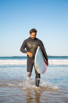 Pensive handicapped surfer walking in sea water with board